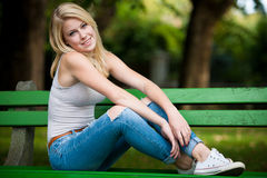 美好的白肤金发的woamn基于一条长凳在公园 免版税图库摄影