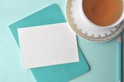 美好的白色瓷瓷杯子用茶、小野鸭铅笔、白色短信卡和水色薄荷的蓝色背景 免版税图库摄影