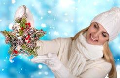 美好的白色被编织的衣裳的一个少妇拿着圣诞节装饰以星的形式 快活的圣诞节 免版税库存图片