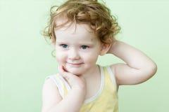 美好的矮小的卷曲女孩微笑 免版税库存照片