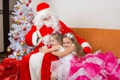 美好的礼服拥抱的圣诞老人女孩 库存图片