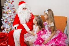 美好的礼服谈话的女孩与圣诞老人 库存照片