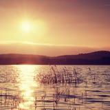 美好的秋天日出或日落与反射在湖水平面上 免版税库存照片