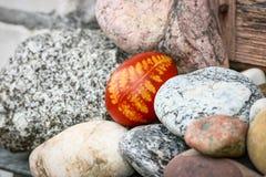 美好的红色在小卵石之间的色的复活节彩蛋 库存照片