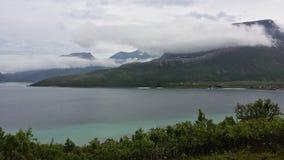 美好的绿色风景在与蓝色海湾和海的夏天在远的背景中 免版税库存照片