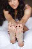 美好的脚,在一个少妇的床上 免版税库存图片