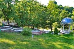 美好的自然在一个清楚的晴朗的下午的公园 一个绿色倾斜和下降下坡导致 免版税库存图片