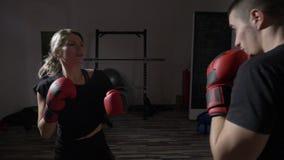 美好的艰苦训练为与她的男性箱子教练的大比赛的适合女性kickboxer在健身房慢动作的体育演播室- 影视素材