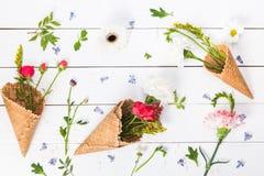 美好的花卉构成顶视图与奶蛋烘饼锥体的 免版税图库摄影