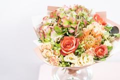 美好的花束春天 与各种各样的花的布置在玻璃花瓶的颜色在桃红色桌上 明亮的室,白色 库存照片