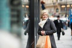 美好的资深妇女窗口购物在城市 冬天 库存图片