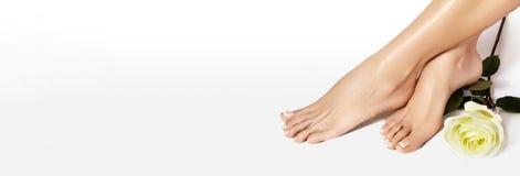 美好的赤脚 钉牢涂清漆,在白色颜色的法式修剪 修脚,在美容院概念的指甲油 免版税库存图片
