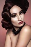 美好的赤裸时装模特儿画象与波浪发样式、帽子和黑暗的构成的在红色背景 免版税库存照片
