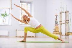 美好的运动的适合信奉瑜伽者妇女实践瑜伽转弯常设asana在健身屋子 免版税图库摄影