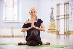 美好的运动的适合信奉瑜伽者妇女实践瑜伽asana Garudasana老鹰姿势在健身屋子 免版税库存照片