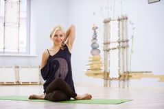 美好的运动的适合信奉瑜伽者妇女实践瑜伽asana Garudasana老鹰姿势在健身屋子 库存照片