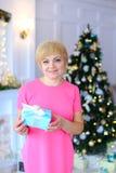 美好的逗人喜爱的妇女身分和微笑,举行在bac的礼物盒 免版税库存图片
