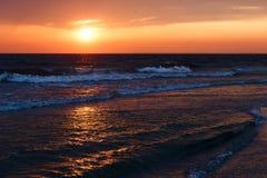 美好的金黄日落在有饱和的天空和云彩的海 反射在水中 岩石沿海线 平安的平静的lan 免版税库存图片