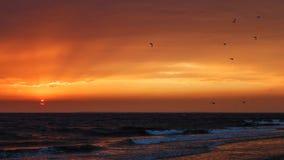 美好的金黄日落在有饱和的天空和云彩的海 反射在水中 岩石沿海线 平安的平静的lan 免版税库存照片