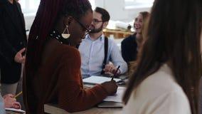美好的非洲年轻女人与在膝上型计算机,愉快的不同种族的商人的文件一起使用在办公室背景中 影视素材