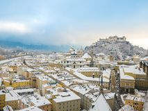 美好的风景冬天风景在历史的市有多雪的屋顶、大教堂和著名堡垒的Hohensalzburg b萨尔茨堡 库存照片