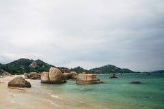 美好的风景有海洋,完善的海滩,大石头,树,天蓝色的水看法  背景概念能源图象 概念旅行 免版税图库摄影