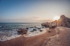 美好的风景,在日落的含沙岩石海海湾 免版税库存图片