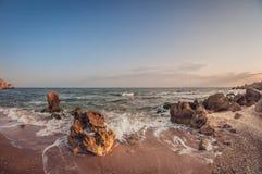 美好的风景,在日落的含沙岩石海海湾 免版税库存照片