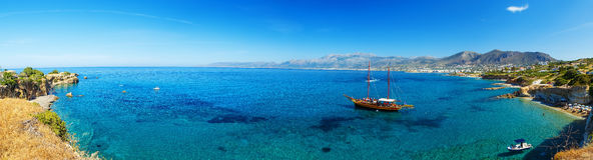 美好的风景-传统古板的巡航小船全景靠码头对沙子岸和五颜六色的蓝色天蓝色 免版税库存图片