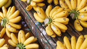 美好的黄色束与价牌的小香蕉在街市上的竹柜台,泰国 股票录像