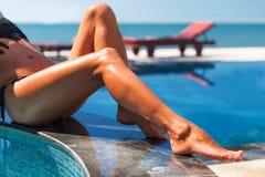 美好的年轻亭亭玉立的妇女egs在游泳池附近晒日光浴 库存图片