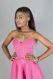 美好的黑人妇女立场确信的桃红色礼服 免版税库存照片