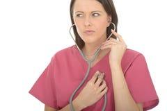 美好的年轻关心的女性Listening To Her Own医生心跳的画象 库存照片
