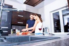 美好的年轻夫妇在厨房里 免版税库存图片