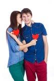 美好的年轻夫妇在手上的拿着小红色纸心脏 库存照片