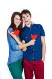 美好的年轻夫妇在手上的拿着小红色纸心脏 免版税图库摄影