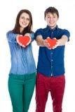美好的年轻夫妇在手上的拿着小红色纸心脏 免版税库存图片