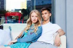 美好的年轻夫妇坐长沙发在一个温暖的夏天晚上 西班牙人,白种人女孩 免版税库存图片