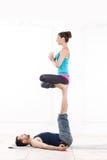 美好的年轻夫妇实践的Acro瑜伽 免版税库存照片