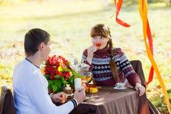 美好的年轻夫妇有野餐在秋天公园 愉快的Famil 免版税库存照片