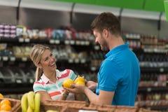 美好的年轻夫妇购物在杂货超级市场 免版税图库摄影