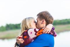 美好的年轻夫妇画象在亲吻在湖附近的爱的 免版税库存图片