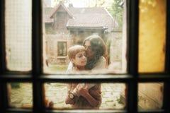 美好的年轻婚礼夫妇在老木房子附近站立 库存图片