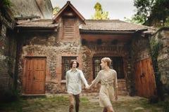 美好的年轻婚礼夫妇在老木房子附近站立 免版税库存照片