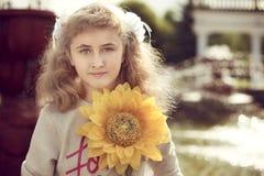 美好的10岁站立在喷泉附近的女孩,举行a 库存照片