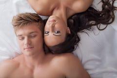 美好的年轻异性爱夫妇在床上 库存图片