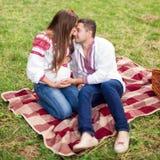 美好的年轻怀孕的夫妇在全国乌克兰样式穿戴了有野餐在秋天公园 母道和家庭幸福c 图库摄影