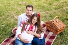 美好的年轻怀孕的夫妇在全国乌克兰样式穿戴了有野餐在秋天公园 母道和家庭happyness c 库存图片