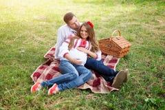 美好的年轻怀孕的夫妇在全国乌克兰样式穿戴了有野餐在秋天公园 母道和家庭happyness c 图库摄影