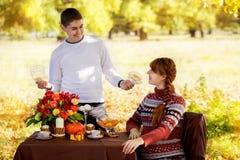 美好的年轻怀孕的夫妇有野餐在秋天公园 Ha 库存照片